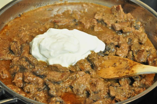 Sour cream added to beef and sauce in metal skillet