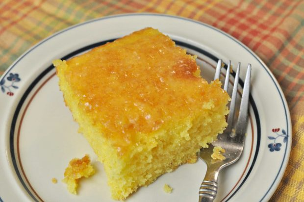 Slice of lemon cake on plate with a fork... ready to eat.