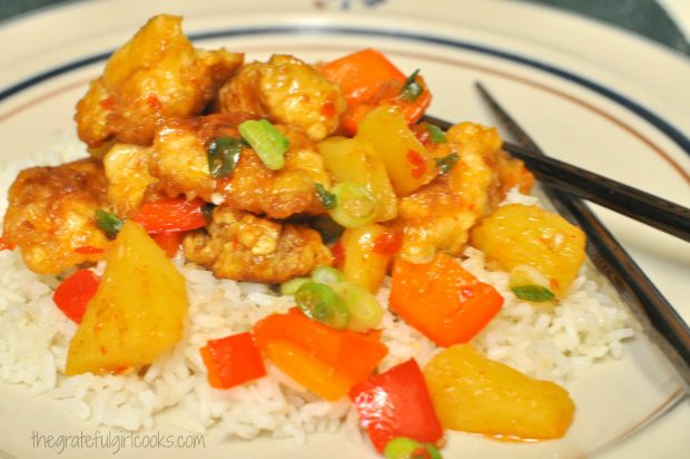 Sweet fire chicken is served on top of white rice.