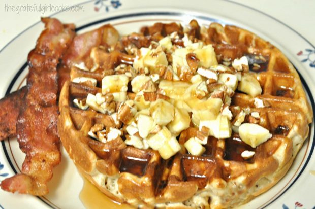 Banana Waffle with pecans and bananas, with bacon on side of plate
