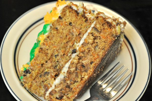 A big slice of Edie's carrot cake, on plate with a fork.