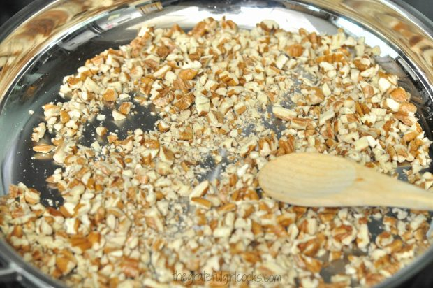 Dry toasting chopped pecans in skillet, for decorating Edie's carrot cake.