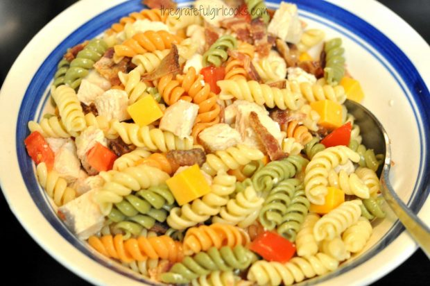 Pasta, bacon, tomatoes and cheese are mixed together for club salad