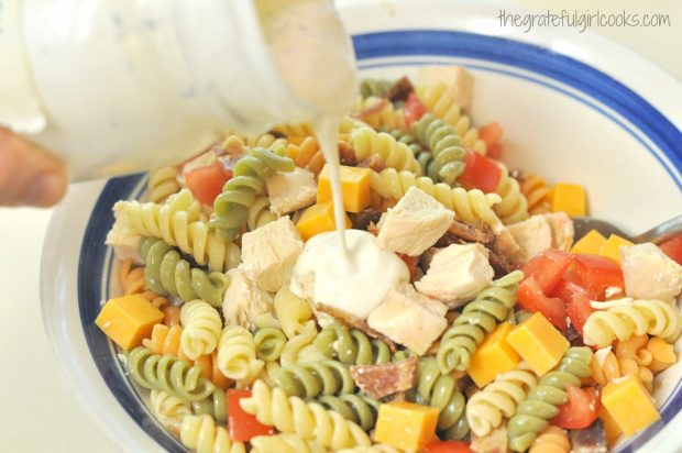 Creamy dressing is poured over pasta salad