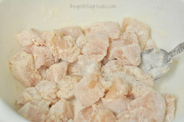 Excess flour is shaken off chicken breast cubes before cooking.