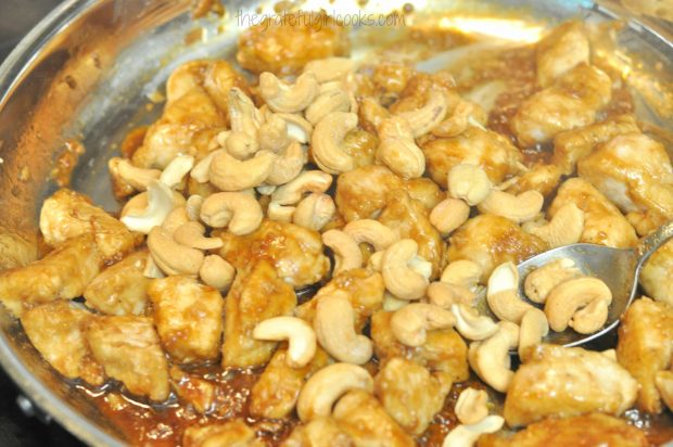Cashews are added to chicken and sauce.