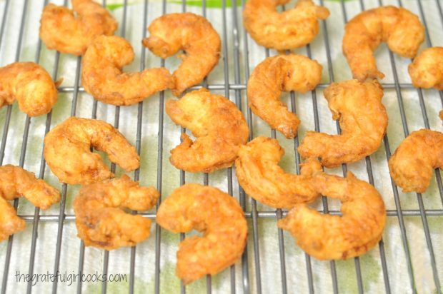 Fried shrimp drain on wire rack before serving.