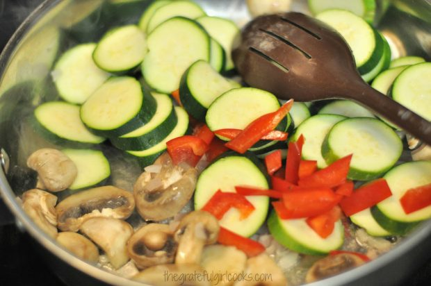 Sliced zucchini and red peppers are added to the mushrooms in the skillet.