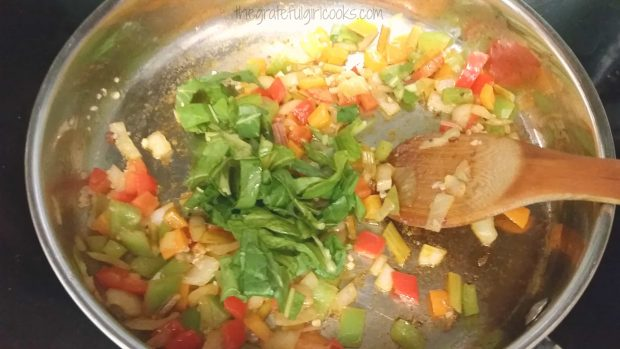 Swiss chard, bell peppers and onions are cooked before adding to the dish.