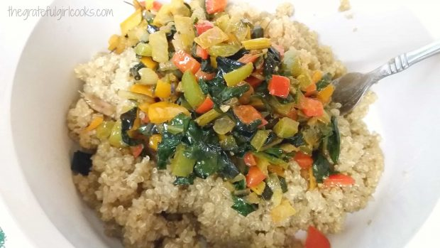 The cooked veggies are added on top of the cooked quinoa in a bowl.