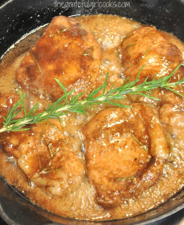 Cooked pork with rosemary sprig in skillet