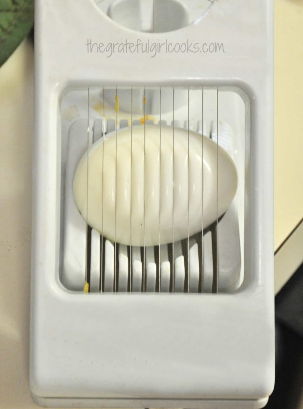 Hard boiled egg in slicer for potato salad garnish.
