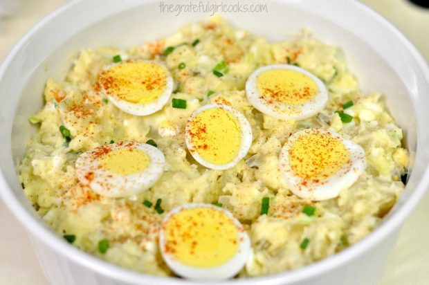 Potato Salad in white bowl, with sliced egg garnish.