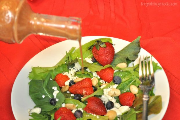 Pouring strawberry balsamic vinaigrette over salad, with strawberries and blueberries.