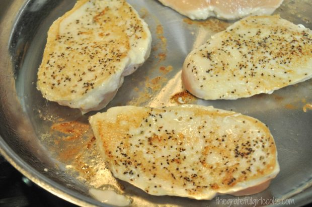 Browned chicken breasts cooking in skillet