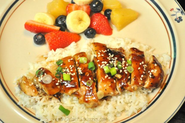 Teriyaki chicken, sliced and served on rice, with fruit on side