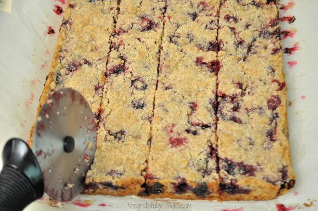 Blackberry bar cookies are cut into squares with pizza cutter