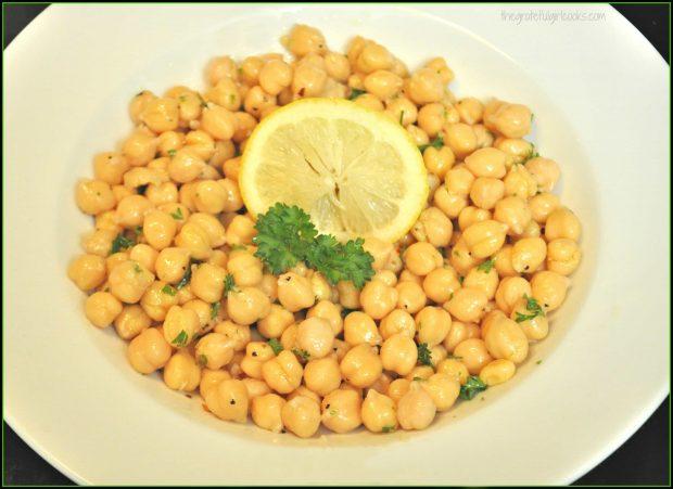 Lemony chickpea salad with parsley and lemon garnish in white bowl