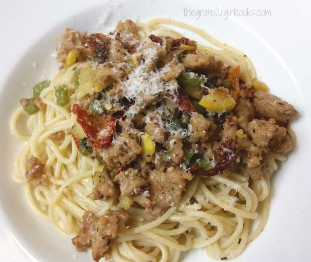 The finished pasta with Italian sausage is sprinkled with Parmesan and served in a white bowl.