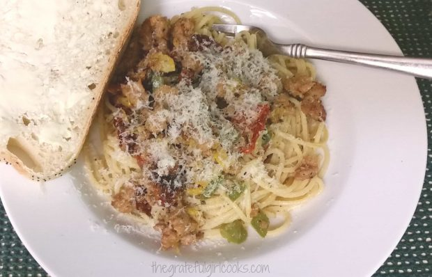 A slice of buttered sourdough bread is served along with the pasta with Italian sausage.