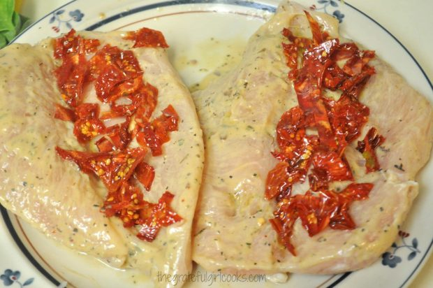 Sun dried tomatoes are placed on one side of the chicken breast.