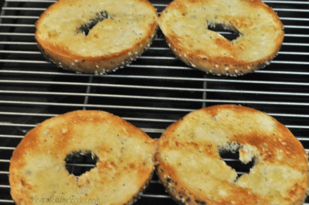 Buttered bagels are broiled until golden brown.