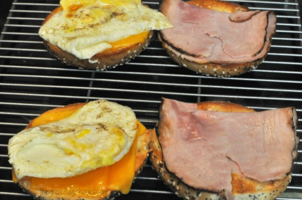 Fried egg and ham slices are added to breakfast sandwich.