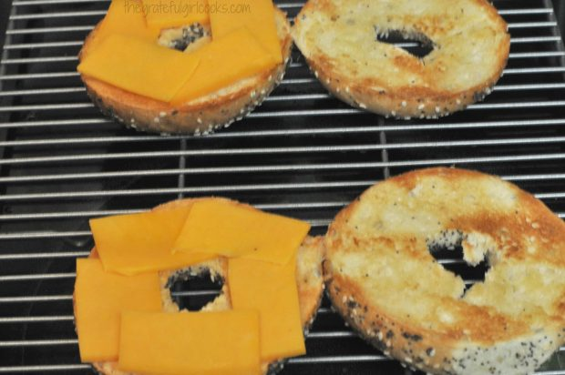 Thin cheese slices are placed on bagel halves.