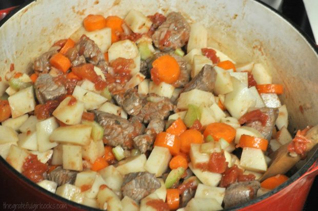 Potatoes, carrots, tomatoes are added to beef stew meat in pan.