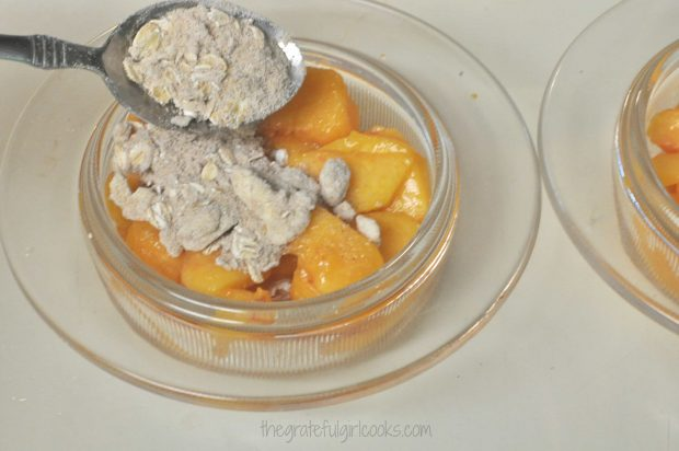 Streuesel topping is placed on top of peaches.