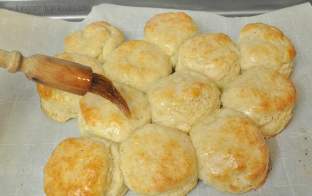 Melted butter being brushed on top of biscuits