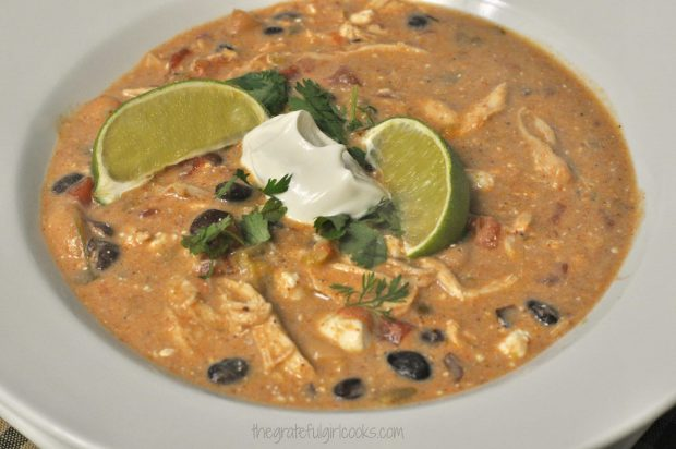 Green Chile Chicken Crockpot Enchilada Soup is garnished with sour cream, lime wedges and cilantro to serve.