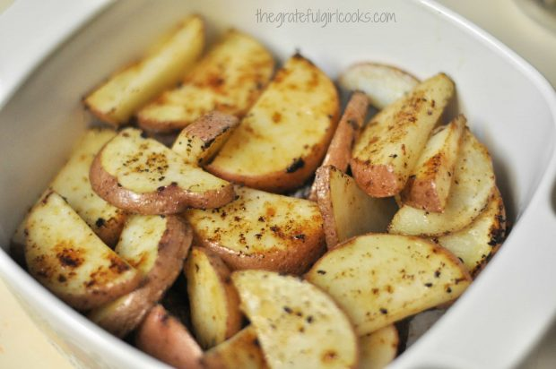 Cooked red potato slices are placed on top of Italian sausage in baking dish.