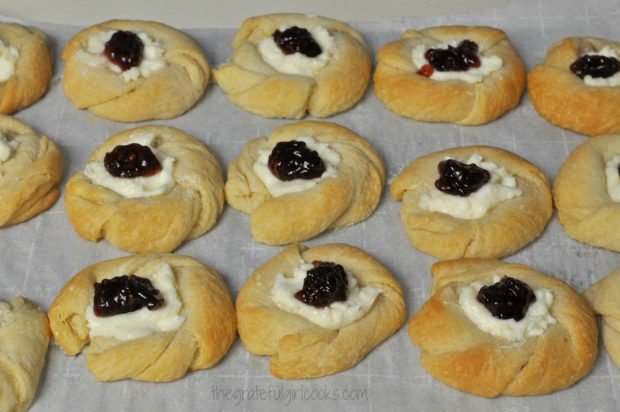 A dollop of raspberry jam is added to each baked danish pastry.
