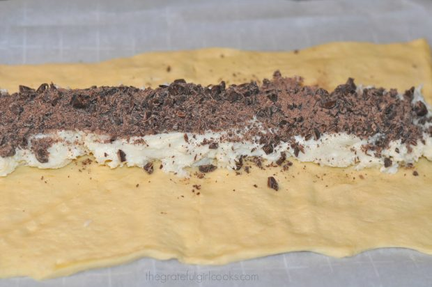 Chopped chocolate sprinkled onto cream cheese filling on dough