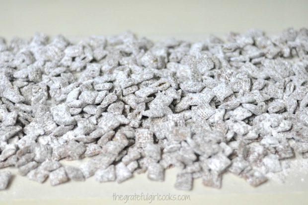 Chocolate Peanut Butter Muddy Buddies are laid on wax paper, to dry.