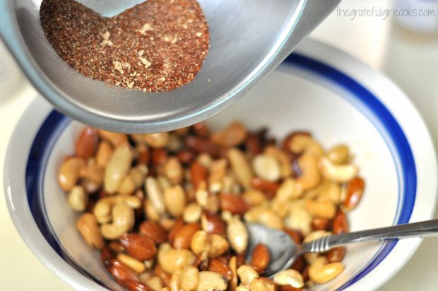 Spice mixture is poured into bowl of butter roasted nuts.