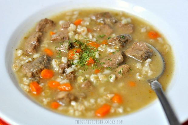 Soup with barley, meat, carrots and broth in white bowl with spoon