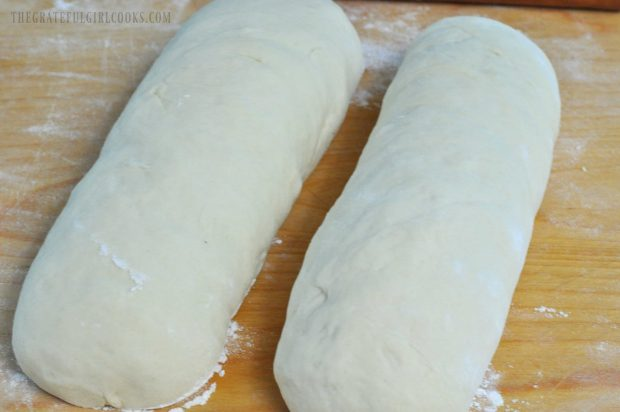 Two loaves of homemade white bread dough on wood cutting board