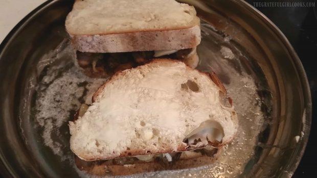 The pork tenderloin sandwich is grilled in a skillet.