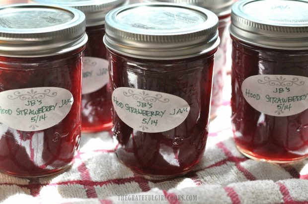 Jars of jam with labels, canned and cooling on dish towel
