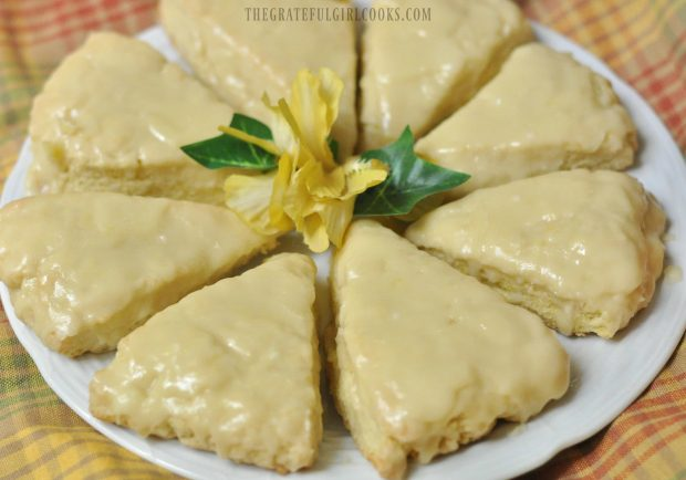 Lemon cream scones, served on white plate with yellow flower on top