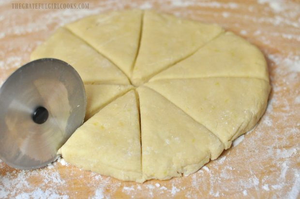 Lemon cream scone dough is cut into 8 wedges with pizza cutter