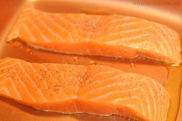 Two salmon fillets searing in copper skillet