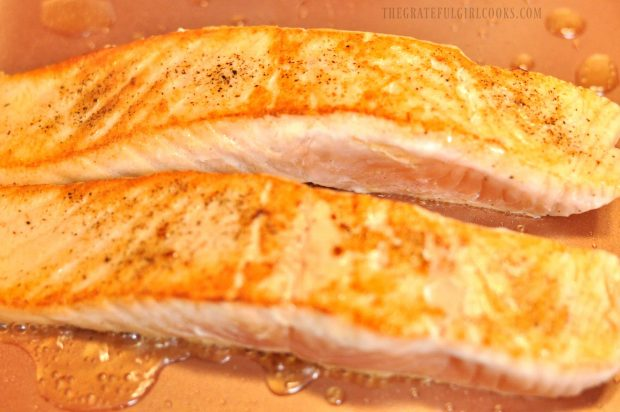 Two golden brown seared salmon fillets in skillet