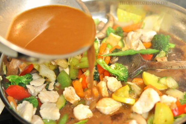 An Asian-inspired sauce is added to the skillet full of chicken veggie stir fry.