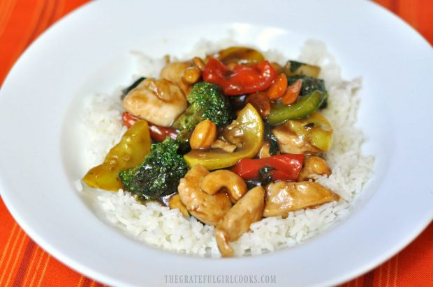 Chicken veggie stir fry is served on a bed of white rice.