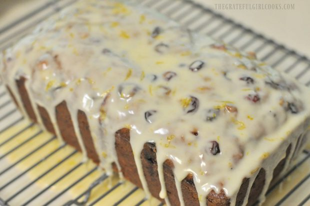 Cranberry orange loaf with orange icing on wire rack.
