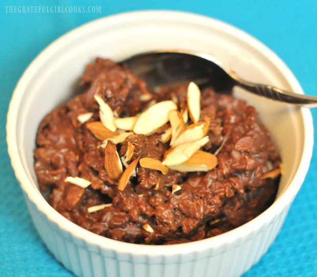 Healthy chocolate oatmeal is topped with almonds after being microwaved.