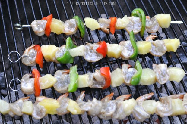 Shrimp, pineapple and peppers on skewers on BBQ